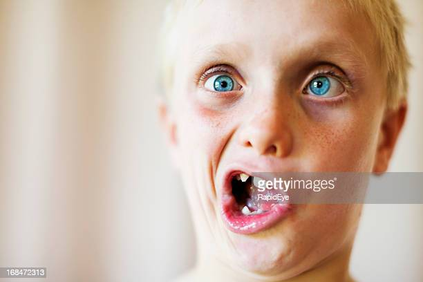 Cute blond 8 year old boy makes zany face