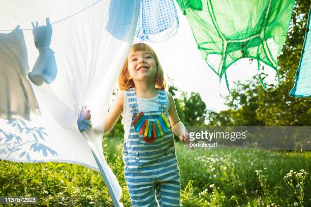 cute blond boy looking through laundry - clothesline stock pictures, royalty-free photos & images