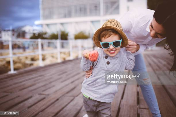 Cute blond boy with his mum eating ice cream