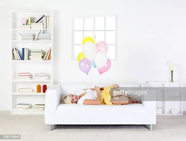 cute blond female laying on sofa holding balloons - tidy room stock pictures, royalty-free photos & images
