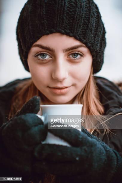 süße blondine mit schwarzen handschuhen und mütze tee trinken - mütze stock-fotos und bilder