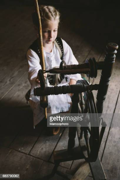 Cute blond little child girl wearing traditional costume sitting by wooden spinning wheel in old house