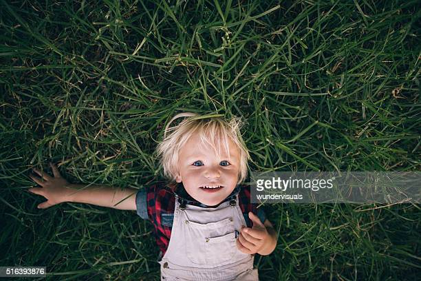 cute blonde child lying on the grass - preschool age stock pictures, royalty-free photos & images