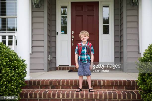 cute blonde curly headed boy waits for school bus on front steps - first day of school stock pictures, royalty-free photos & images