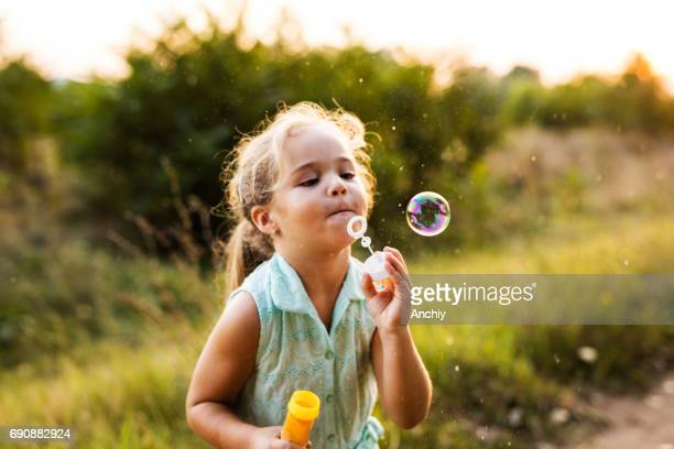 cute blonde girl blowing soap bubbles at the countryside - dog eats out girl stock pictures, royalty-free photos & images
