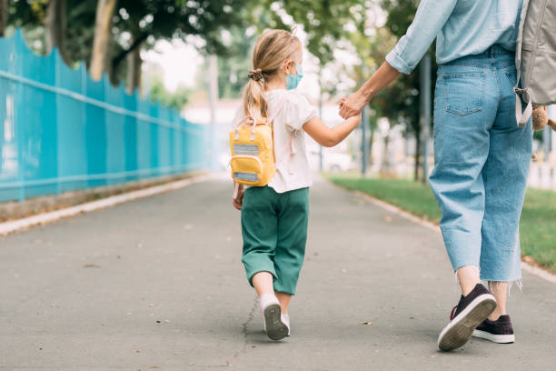 cute blonde girl wearing a protective mask being taken to school by her mom/ a babysitter - parents and children at school stock pictures, royalty-free photos & images