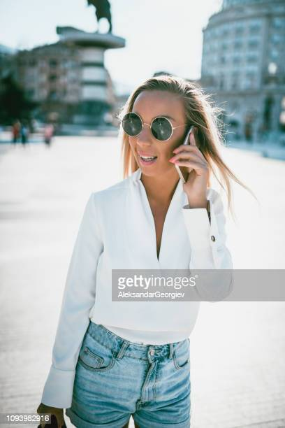 Cute Blonde In Casual Clothing Making a Phone Call In The City Square