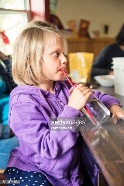 Cute blonde little girl sipping water at dinner at home.
