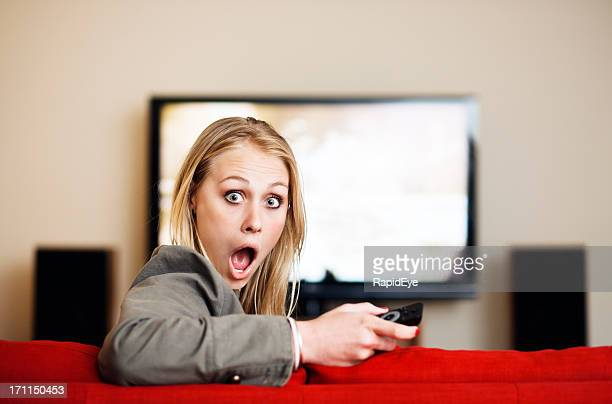 Süße blonde looks Runde, schockiert von TV im Hintergrund
