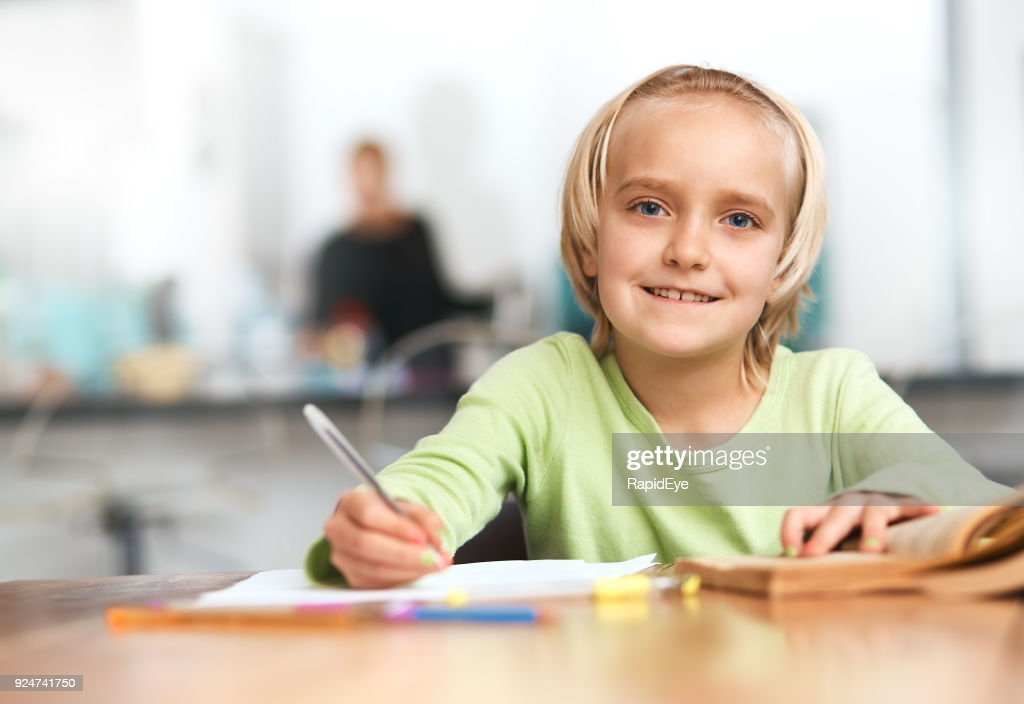 Cute Blonde Schoolgirl Busy With Homework Smiles Happily Stock Photo