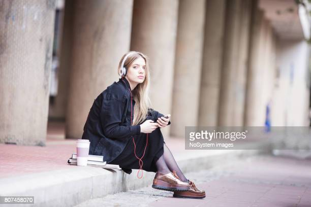 cute, blonde student girl listening music, outdoors - music halls stock pictures, royalty-free photos & images