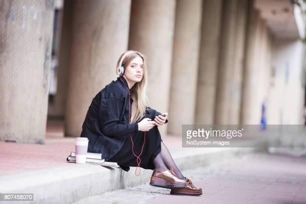 Süße, blonde Studentin Mädchen Musik hören, im freien