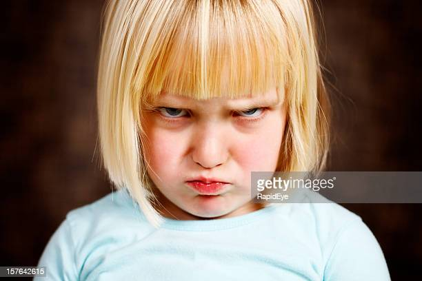 Cute blonde toddler girl scowls at camera