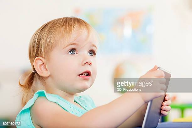 Cute blonde toddler holding digital tablet at daycare center