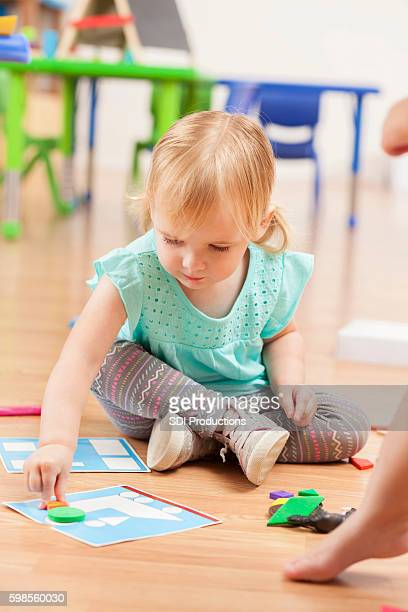 Cute blonde toddler playing with toys on daycare floor