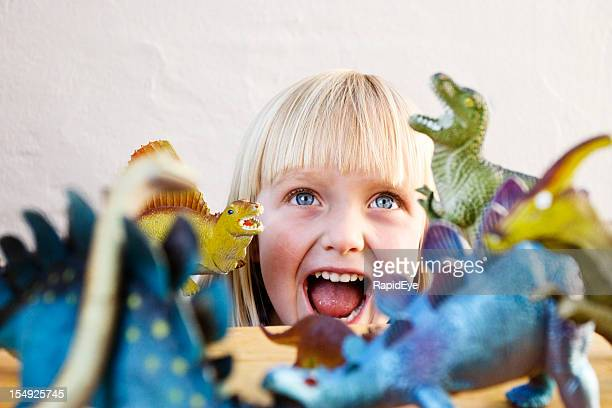 Cute blonde toddler roars at her ferocious toy dinosaurs
