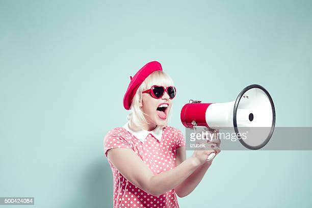cute blonde young woman shouting into megaphone - shouting stock photos and pictures