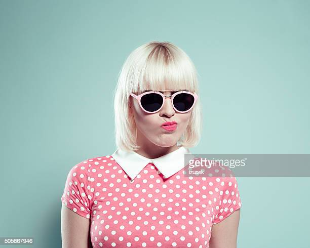 Cute blonde young woman wearing polka dotted dress making faces