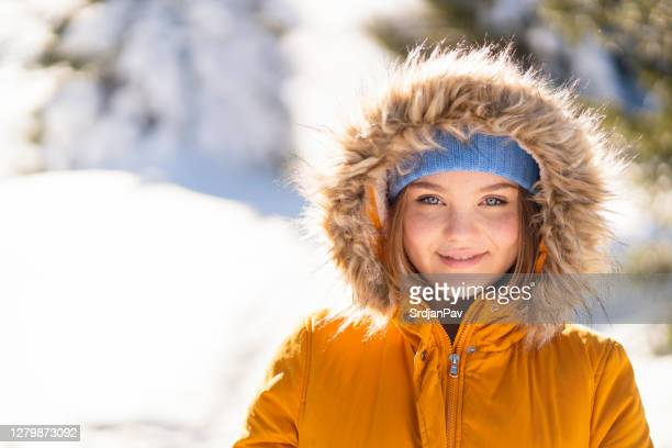 bonita chica de ojos azules en una montaña nevada - coat fotografías e imágenes de stock