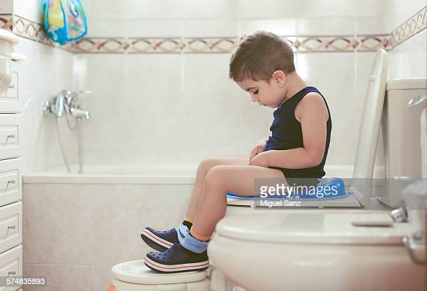 Cute boy, 3-4 years, sitting on the toilet