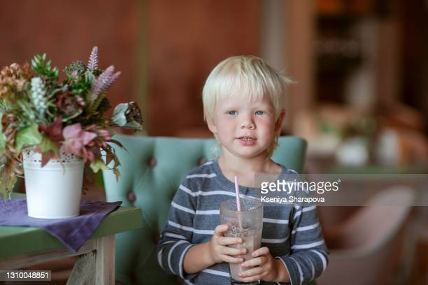 cute boy 4 years old enjoys cocoa in a cafe-stock photo - 2 3 years stock pictures, royalty-free photos & images
