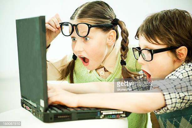 Cute boy and girl nerd looking at laptop with surprise.