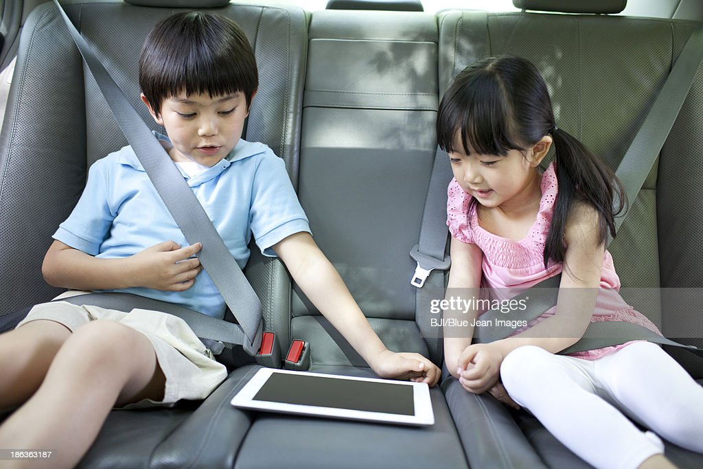 Cute boy and girl playing digital tablet in car : Stock Photo