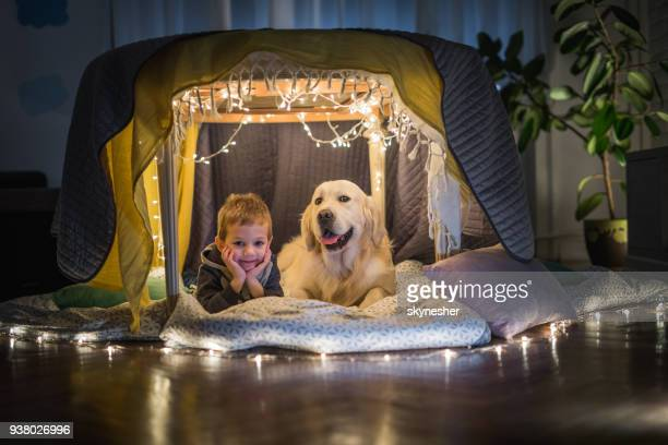 cute boy and his dog relaxing in a tent at home. - children only stock pictures, royalty-free photos & images