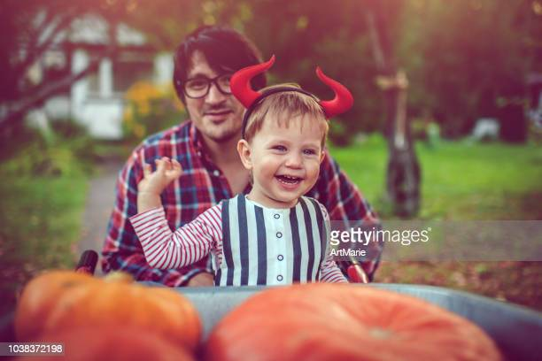 cute boy and his father with pumpkins in autumn - devil costume stock photos and pictures