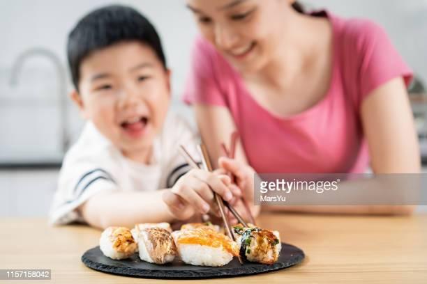 leuke jongen en moeder eten sushi - fish love stockfoto's en -beelden