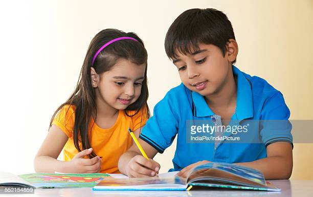Cute boy assisting sister in drawing at table against colored background