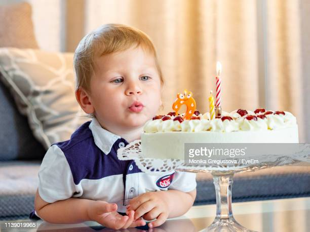 cute boy blowing birthday candles on cake at home - monika gregussova stock pictures, royalty-free photos & images