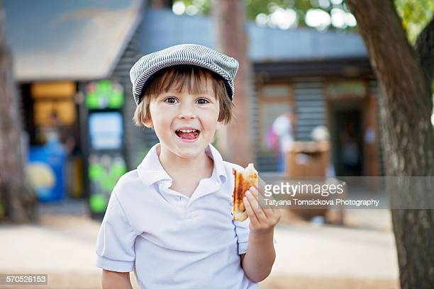 Cute boy, child, eating sandwiches outdoor, summer