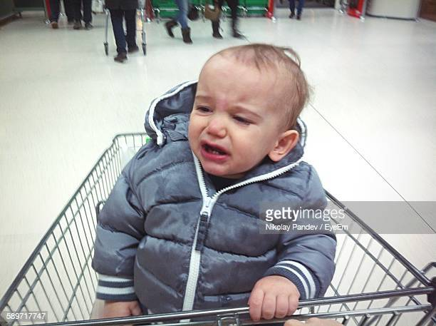 Cute Boy Crying While Sitting In Shopping Cart At Supermarket