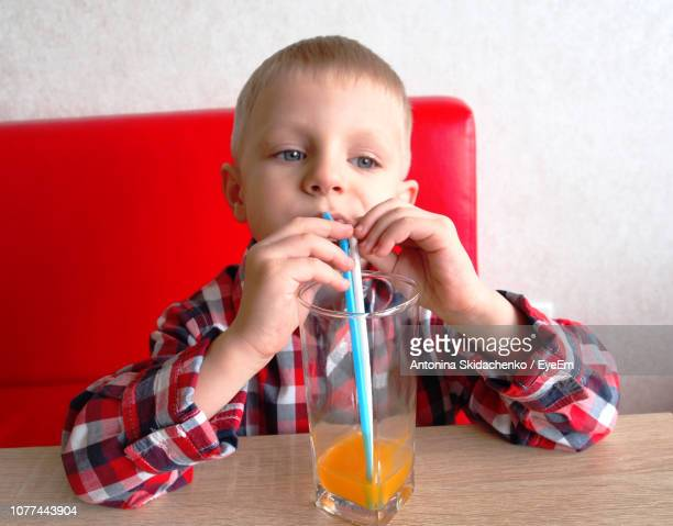 Cute Boy Drinking Juice From Straw At Restaurant