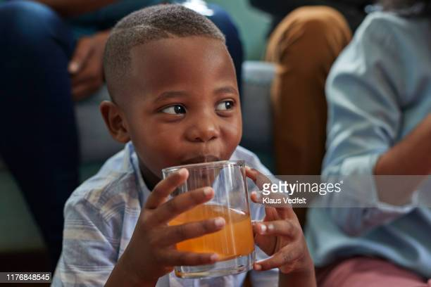 cute boy drinking juice while sitting at home - miscigenado - fotografias e filmes do acervo