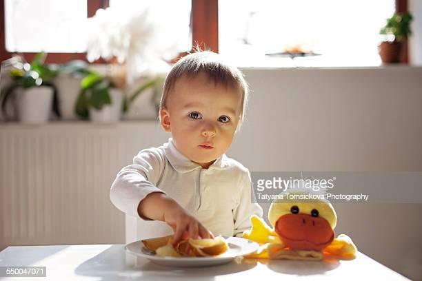 Cute boy, eating lemons at home