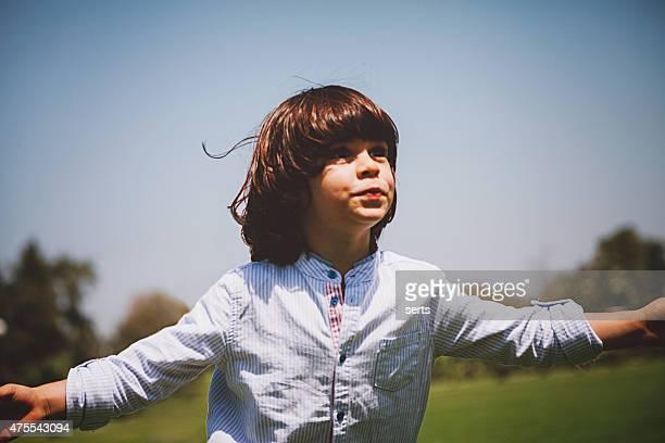 Cute boy feeling a freedom on meadow in nature