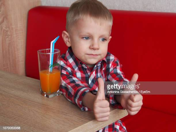 Cute Boy Gesturing Thumbs Up Sign While Sitting By Juice At Restaurant