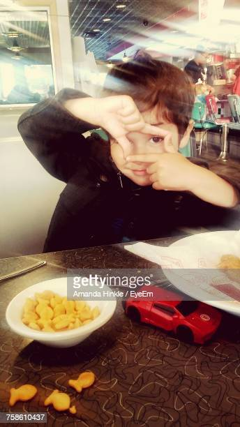 Cute Boy Gesturing While Sitting On Chair At Restaurant