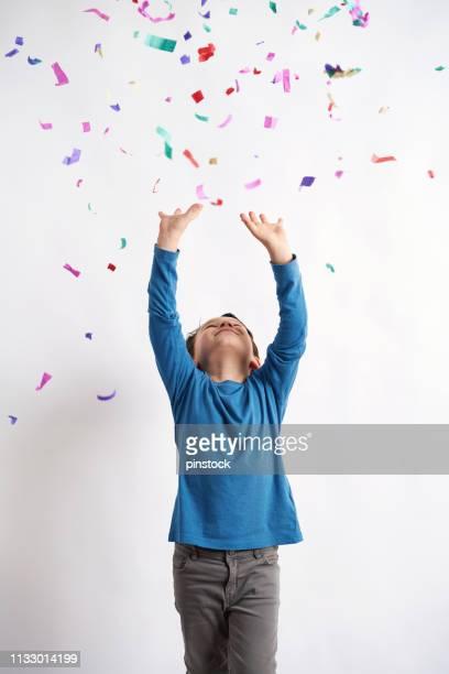 niedlicher junge, der spaß mit konfetti vor weißem hintergrund hat - nur jungen stock-fotos und bilder