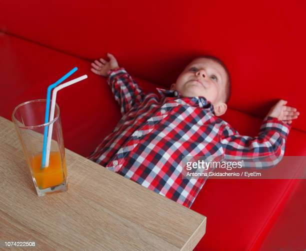 Cute Boy Having Juice While Lying On Sofa In Restaurant
