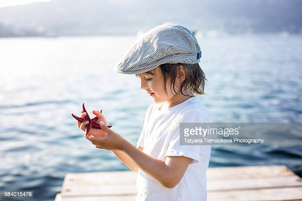 Cute boy, holding beautiful red starfish on the beach, summertime