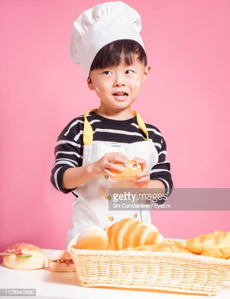 cute boy holding bread crying while standing against pink background - chef's hat stock pictures, royalty-free photos & images
