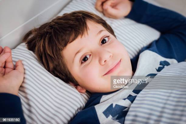 Cute boy in bed staring at the camera
