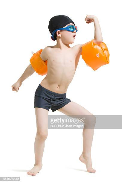 Cute boy in swimsuit with water wings