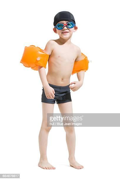 Cute boy in swimsuit with water wings