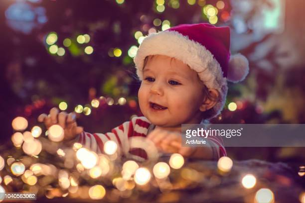 cute boy indoors near christmas tree - christmas stock pictures, royalty-free photos & images
