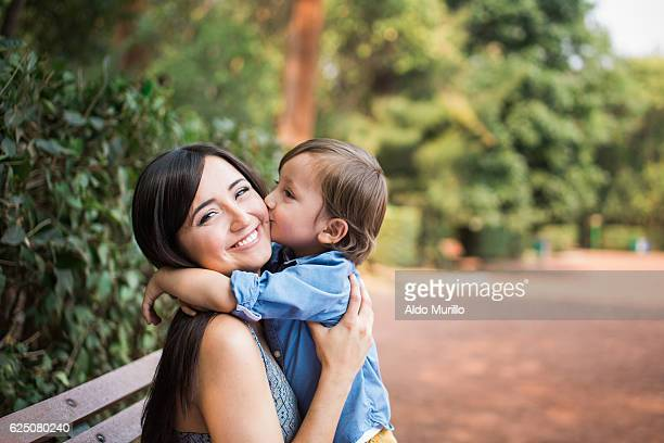 Cute boy kissing mother on the cheek