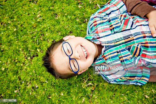 cute boy laughing on grass